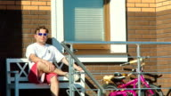 Stylish Man On A Bench Near The House video