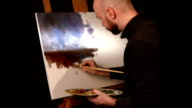 Stylish painter goes on drawing a new painting with oil paints holding the palette in his hand on easel, black background, back light, slow motion video