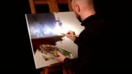 Stylish painter goes on drawing a new painting with sky and ground by oil paints on easel holding the palette in his hand, black background, back light, slow motion video