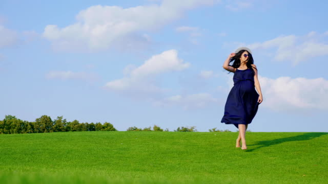 Stylish pregnant woman walking on green grass towards the camera video