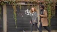 Stylish Young Couple Walking Past Garages On City Street video