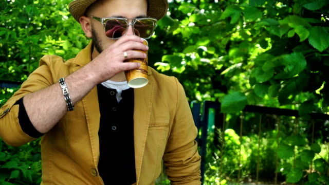 stylish young guy in the Park drinking coffee video