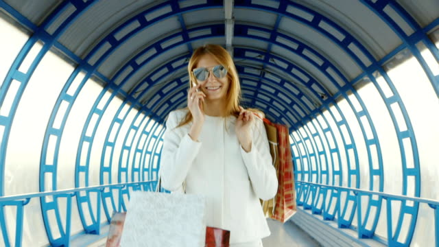Stylish young woman goovrit on the phone walking along the glass transition dyal with packages purchases. successful Shopping video