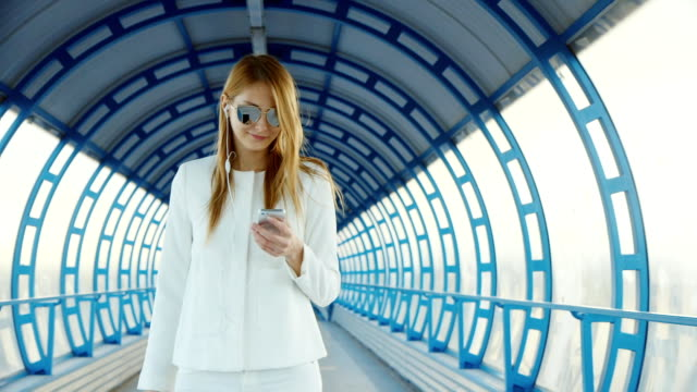 Stylish young woman walking along the glass tunnel. Keeps the phone in your hand, wipe the screen video