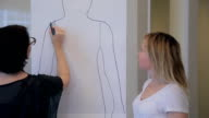 Stylist begins to work on silhouette of client, circled on large sheet of paper video