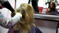 stylist drying hair with round brush. Girl before mirror. FullHD video