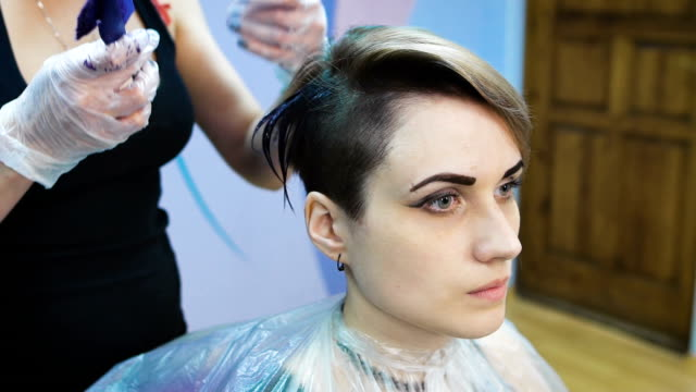Stylist in a beauty studio does hair dye. She decided to cardinally change its image video