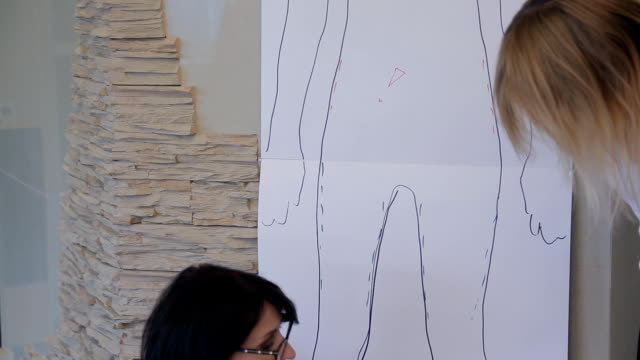 Stylist shows favorable styles by drawn on paper contour of customer video