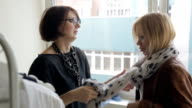 Stylist shows to purchaser how correct tie volume silk scarf video