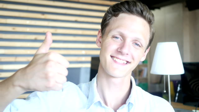 Succesful young man showing thumbs up video