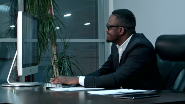 Successful african american businessman sitting at desk, working on generic laptop, typing a message video