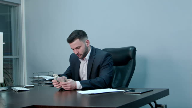 Successful businessman counting his money sitting in office video