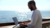 successful businessman uses a laptop in a cafe outdoors on sea background video