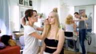 Successful, multi-beauty salon. Several professionals work with their clients. In the frame of an attractive blond woman, she doing makeup video