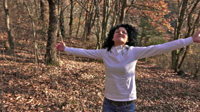 Successful woman raising hands in the forrest, 4 clips compilation. Sony 4K Steadycam shot stock video video