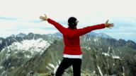 Successful woman raising hands on the top of mountain video