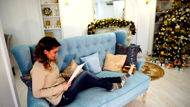 Successful woman reads business papers and sits on couch in decorated room with Christmas tree in daytime video