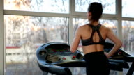 Successful young lady training on treadmill in gym, working hard video