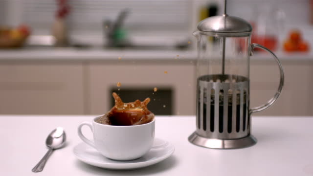 Sugar cube falling into coffee cup in kitchen video