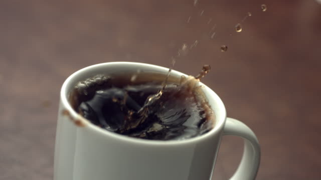 Sugar cube splashing into coffee cup, slow motion video