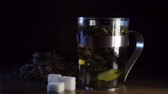 Sugar falls in Peppermint tea slowmotion video