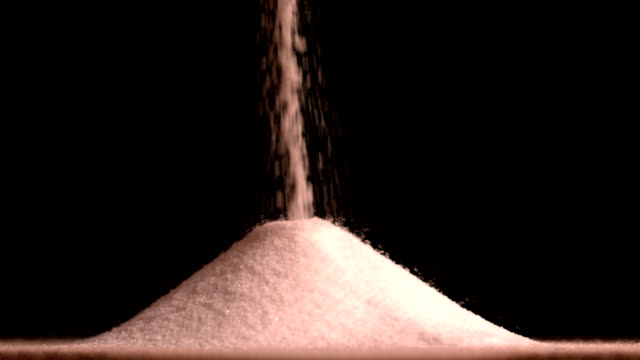 Sugar pouring on black background video