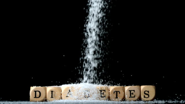 Sugar powder being poured over dice spelling out diabetes video
