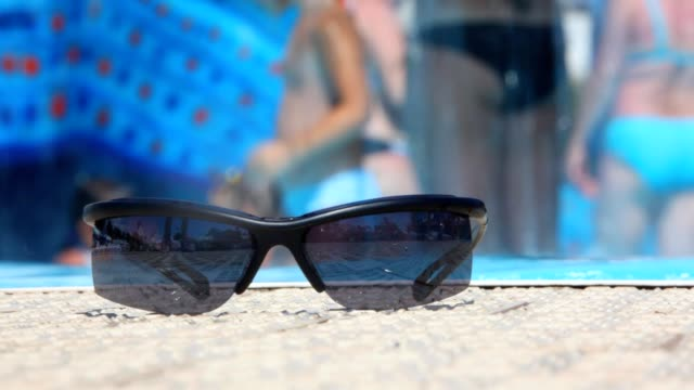 Summer background, people in water park, focus on sunglasses video