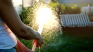 Summer garden smiling woman watering hose flower sunny day in slowmotion video