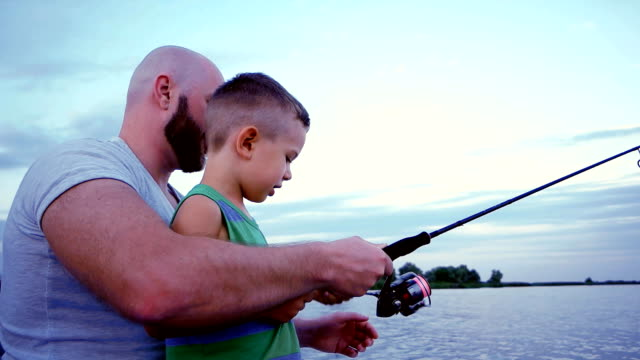 summer holiday for families, man with child on fishing trip, father and son catches a fish with spinning rods, outdoor recreation on the lake, fisherman sitting in a boat video