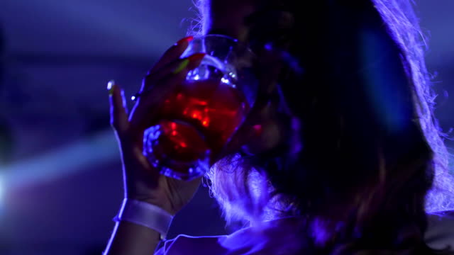 summer party, beautiful woman with beverage on party in blue lights, female have fun and dance at night party video