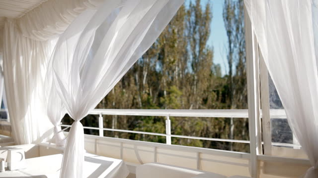 Summer terrace with white furniture  curtains video