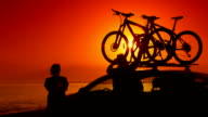 Summer travelers near car with mounted bikes on beach vacation video