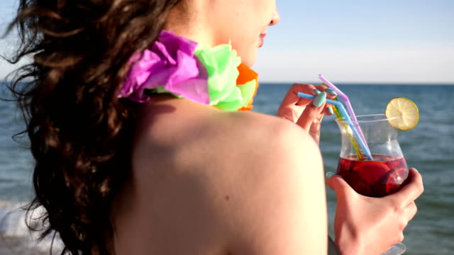 summer vacation on exotic islands, necklace flowers dressed on woman's neck, sexy woman with curly hair drinks colorful cocktail video