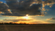 Sun beams through clouds over fields time lapse video