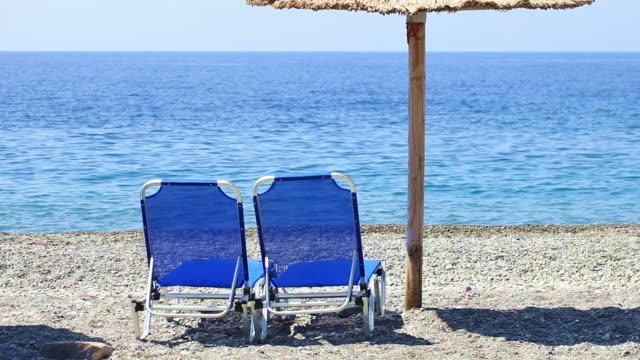 HD: Sun chairs and umbrella on beach video