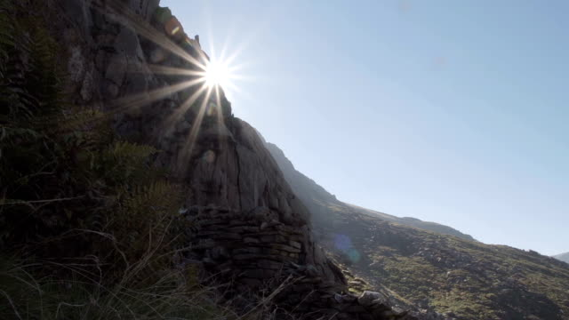 Sun Emerging From Behind A Mountain Cliff Face video
