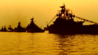 sun in the masts of warships at sunset video