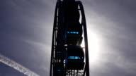 Sun light shine through glass of ferris wheel gondolas, large construction move video