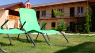 Sun loungers on grass meadow of small tourist hotel video