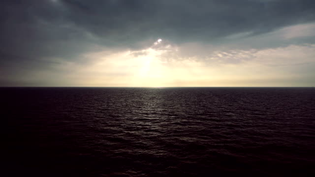 sun rays coming out of clouds and spray on sea video