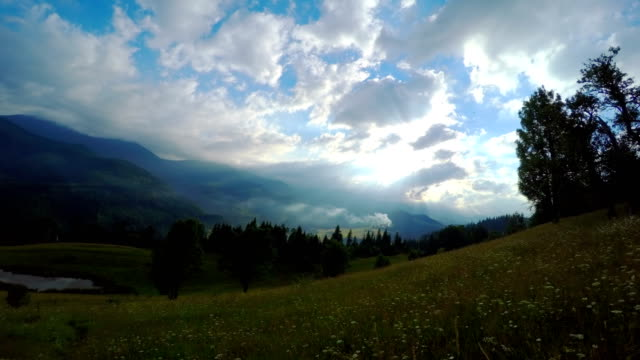 Sun Rays Pass through the Clouds Over the Mountains at Sunset. video