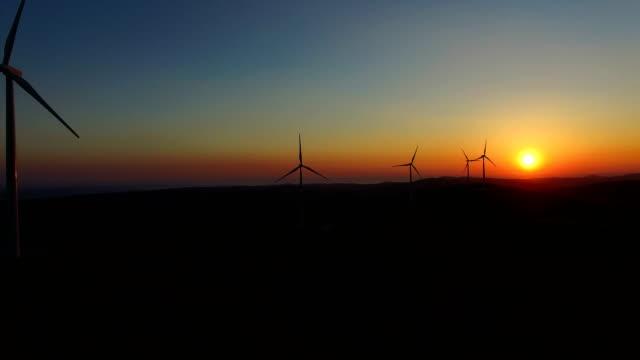 Sun setting behind elegant windmills on a hill video