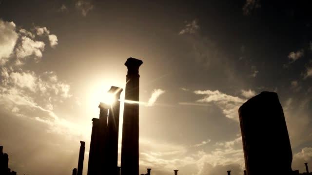 Sun shines through antique columns silhouettes Blue sky ruins ancient town Salamis east Cyprus Famagusta video