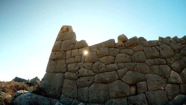 Sun shines through Polygonal laying of The most extant build among ruins close up Adamkayalar Mersin province Turkey video