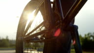 EXTREME CLOSE UP: Sun shining through bmx bike wheel, biker spinning the pedal video
