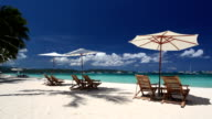 Sun umbrellas and beach chairs on coastline with white sand video
