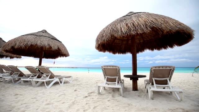Sun umbrellas and beds on caribbean beach video