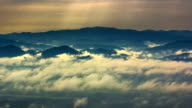 Sunbeams and Fog rolls across flowing over mountains video