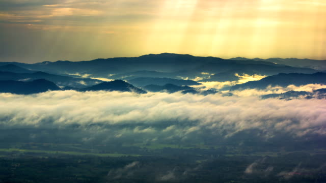 Sunbeams and Fog rolls across flowing over mountains,Time lapse video